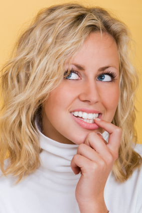 A girl on yellow background biting her nail thinking if she is a candidate for dental implant